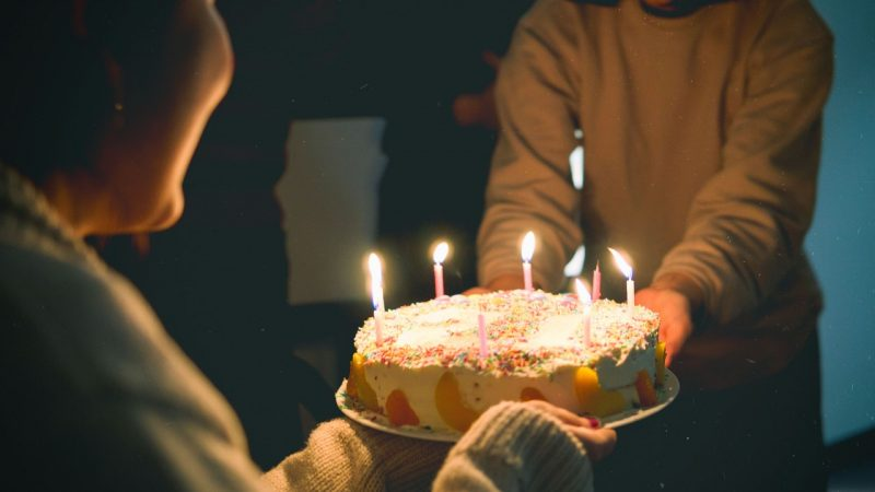 two-people-holding-cake-with-lit-candles-3534022